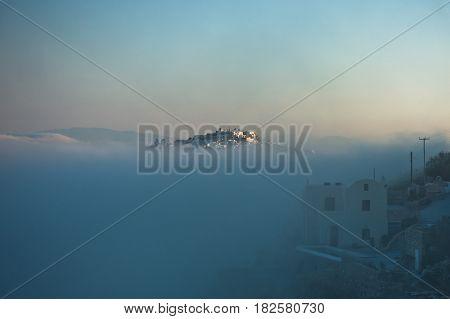 Top of Caldera cliff above the fog at sunny sunrise, village of Imerovigli, Santorini island, Greece