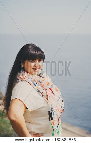 Happy Smiling Beautiful Overweight Young Woman In White T-shirt And Scarf With Anchor Outdoors Near