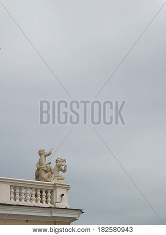 Figurines putti infants-cupids on the balustrade of the Odessa Opera House in Ukraine against the sky