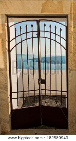 Gate with a view at blue sea and volcano, Imerovigli village, Santorini island, Greece