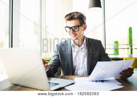 Businessman In Suit And Glasses Working With Laptop And Documents In Office