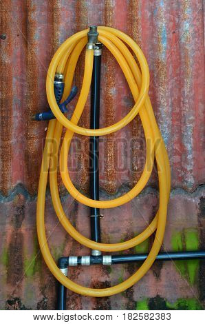 Yellow rubber water hose and black water tube on rusty galvanized wall
