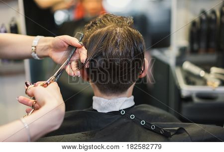 Stylish fashionable young girl in a hairdresser. The portrait of a girl who makes a hipster's hair with shaven temples.