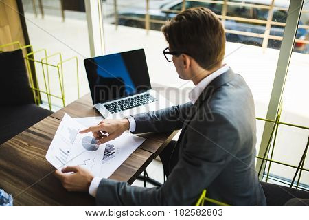 Young Employee Looking At Computer Monitor With Documents During Working Day In Office