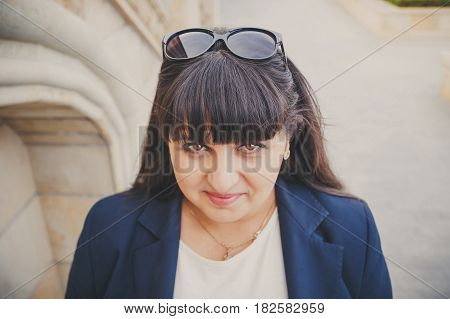 Portrait Of Happy Smiling Beautiful Overweight Young Woman In Dark Blue Jacket Outdoors At The Stree
