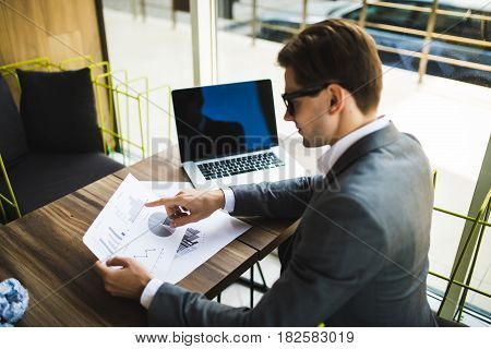 Entrepreneur Working With A Laptop And Holding A Document In A Office
