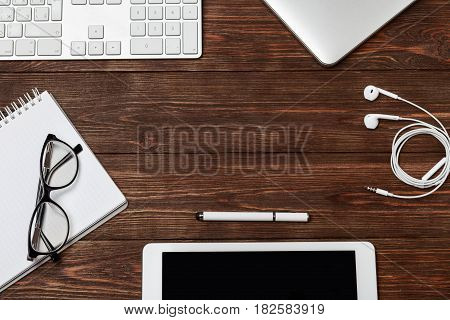 Office workplace with text space. Wooden table with office supplies tablet, coffee, keyboard and book, top view. Modern office workplace. Space for text. Office stuff.