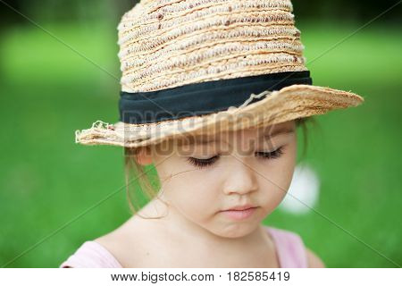 Girl in a straw hat in the park