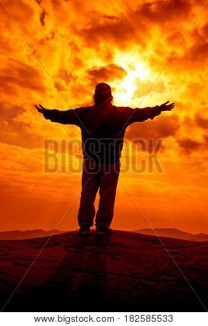 Silhouette of woman arms up outstretched for pray with sunlight on orange sky. Christian praise on hill thanksgiving day background. Freedom and vigorous or powerful concept.