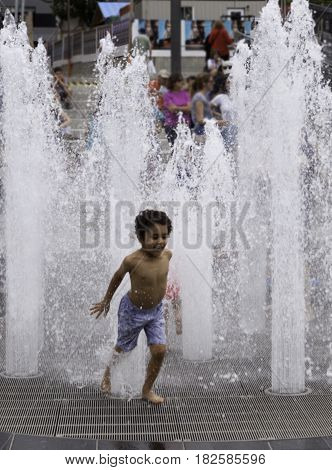 Montreal, Quebec - June 27, 2015 - Vertical of a young boy running out of the automated water fountains at the International Jazz Festival in downtown Montreal, Quebec on a bright day at the end of June.