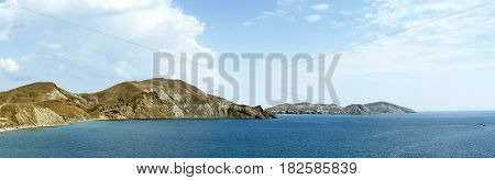 The quiet sea in the summer afternoon against the background of mountains. Coastline. Koktebel. Crimea