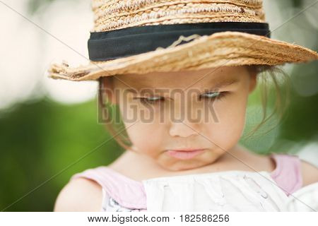 Portrait of angry child in a straw hat