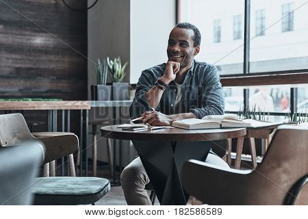 Young and smart. Good looking young man keeping hand on chin and looking away while sitting at his working place in the cafe