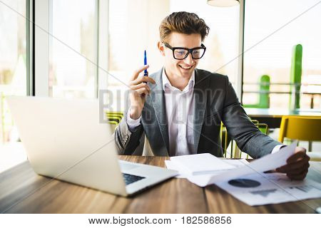 Business Man Working At Office With Laptop And Documents On His Desk. Analyze Plans, Papers, Hands K