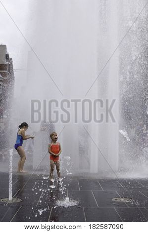 Montreal, Quebec - June 27, 2015 - Vertical of one little girl playing and one little girl crying as the automated water fountains send up huge sprays at the International Jazz Festival in downtown Montreal Quebec on a bright day at the end of June.