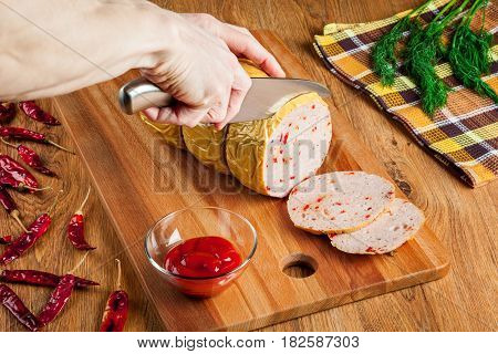 Slicing spicy homemade sausage on a wooden cutting board closeup