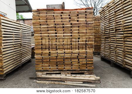 Stack of new wooden boards and studs at the lumber yard. Wooden plates on piles for furniture materials
