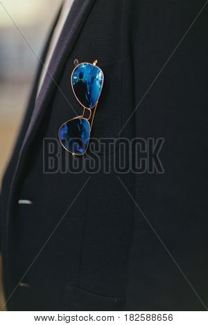 Blue sunglasses hang from a jacket's pocket