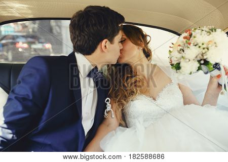 Just Married Couple Kiss Sitting On The Back Seat In An Old Car