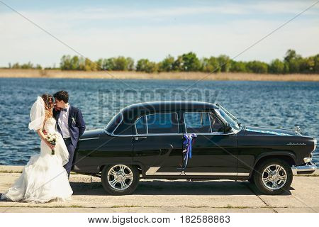 Newlyweds kiss leaning to an old car which stand on the sea shore
