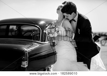Bride Leans To A Groom While He Kisses Her Shoulder Standing Under The Lights Of Summer Sun
