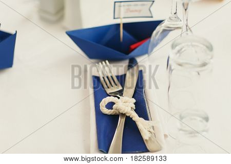 Rope twines cutlery lying on the blue serviette