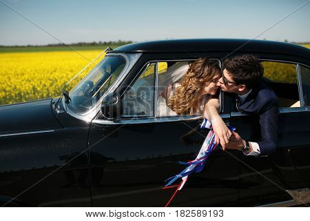 Groom Kisses Bride's Nose Reaching To Her Through The Car's Window