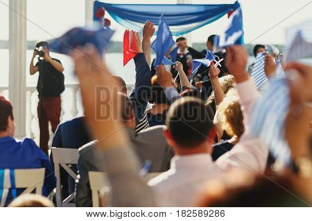 Guest greet newlyweds waving the little flags