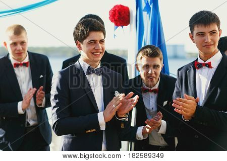 Groom and groomsmen wait for a bride behind a wedding altar