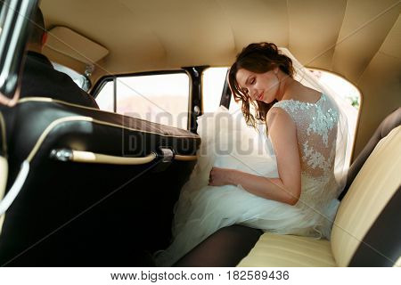 Beautiful bride sits down in an old car