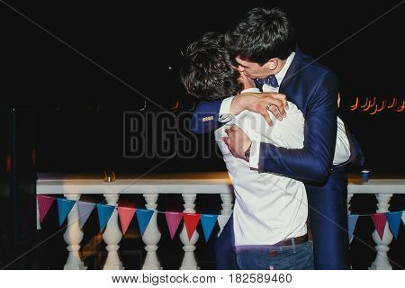 Groom kisses his friend standing on the shore at night