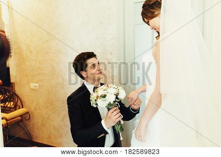 Fiance Stands On The Knees Before A Bride Holding A Wedding Bouquet