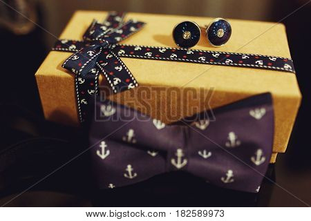 Violet bow tie with a anchor design lie behind a box with cuff links