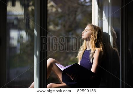 Daydreaming and relaxing. Pretty girl or young woman student teenager with cute young face and blond long hair in dress sleeping with book at open window on sill on sunny day on urban background