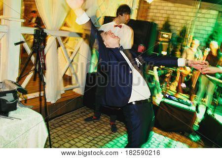Happy groom looks crazy dancing in the restaurant hall