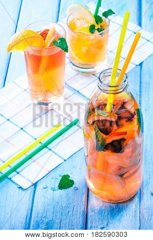 Detox water with various citrus fruit. Bottle and two glasses with slices of orange, blood orange, lemon and grapefruit. Blue plank background