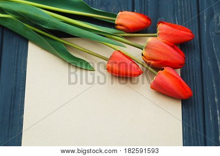 Red Tulips Lying In A Row On Craft Paper Background