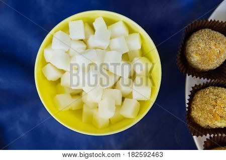 Sugar refined cubes in a yellow plate with cakes on a blue table