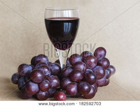 glass of red wine and red grapes
