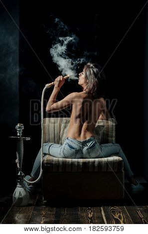 arabic tradition naked girl smoking hookah pretty woman with sexy back and body in jeans sitting on eastern chair on wooden floor with shisha bong or kalian on black background