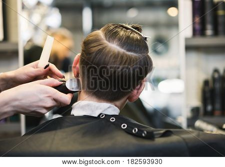 In the hairdresser's girl make a hairstyle with a machine shaving whiskey. In the hands of a master hair clipper.