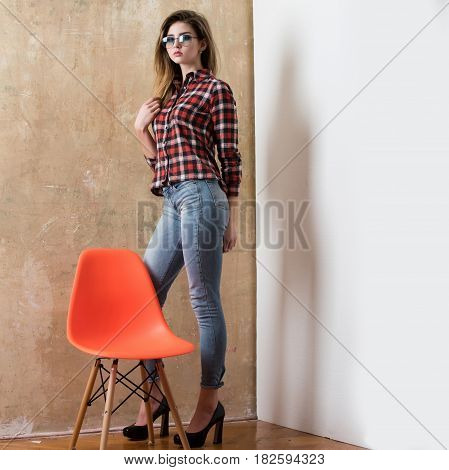 Interior and furniture. Pretty girl or sexy woman fashion model with stylish long hair in eyeglasses red plaid shirt jeans standing in shoes on high heels at orange chair on beige and white wall