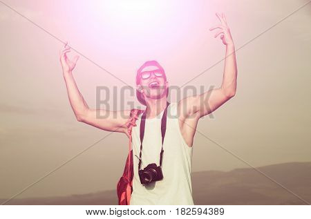 Photography and hobby. Happy handsome man photographer with camera or traveler in stylish fashionable sunglasses and cap with hands gesture raised to grey sky on sunny summer day