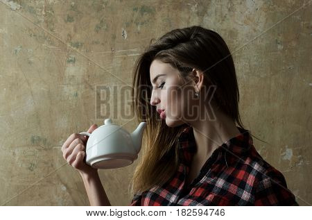 Pretty girl or beautiful woman with stylish blond long hair in red plaid shirt holding white ceramic tea pot teapot on beige wall. Teatime and ceremony