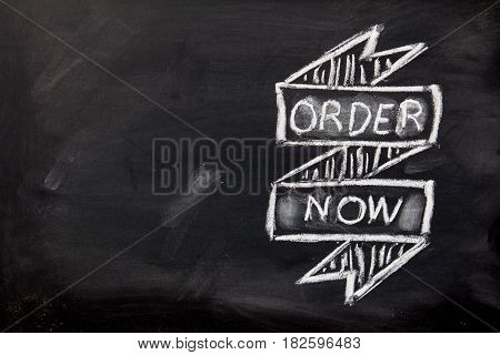 Grunge ribbon draw by white chalk with order now wording on black board background