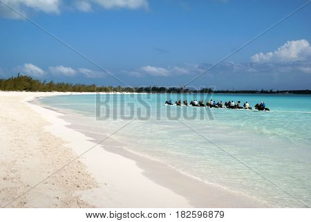 The group of tourists riding horses along the beach on uninhabited island Half Moon Cay (Bahamas).