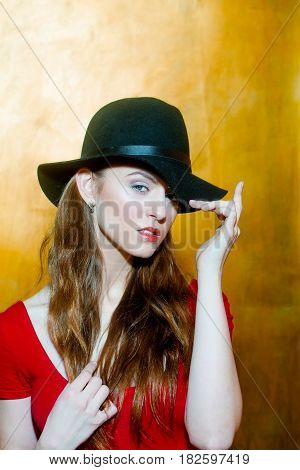 Pretty girl or beautiful fashion woman with long blond hair wearing stylish black hat and red tshirt on beige wall