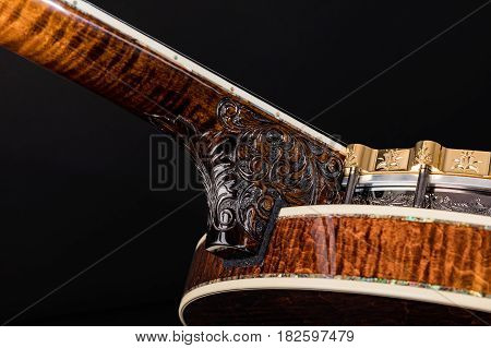 Banjo on black background. Carved wooden neck Banjo. Beautiful carved painting.