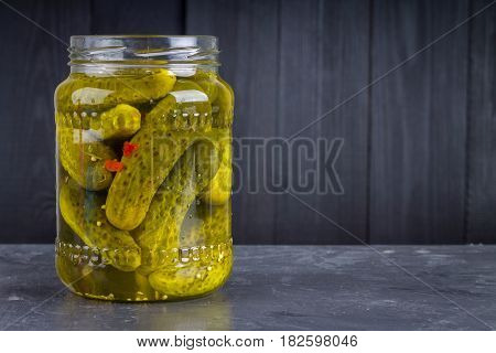 Pickled Gherkins Or Cucumbers In Glass Jar On A Gray Background