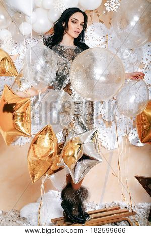 decoration set of festive golden balloons sledge star feathers white snowflakes pretty woman or cute sexy girl in silver sequins dress has brunette hair. party and holiday celebration